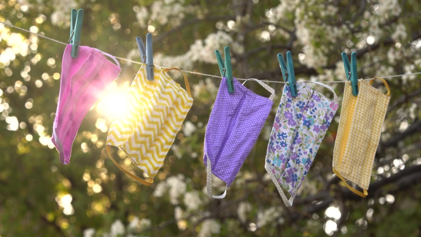 A reusable DIY fabric cotton mask is dried on a clothesline in the open air for reuse. Covid-19 Pandemic. Cloth Face Mask Washing, Drying, Cleaning, Disinfection and Sterilization | Shutterstock HD Video #1053222221