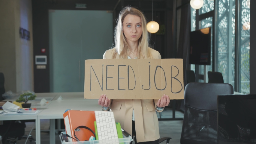 Fired unhappy blonde woman showing job search banner sign indoors while leaving old office during coronavirus outbreak. Problems of quarantine. Global unemployment.