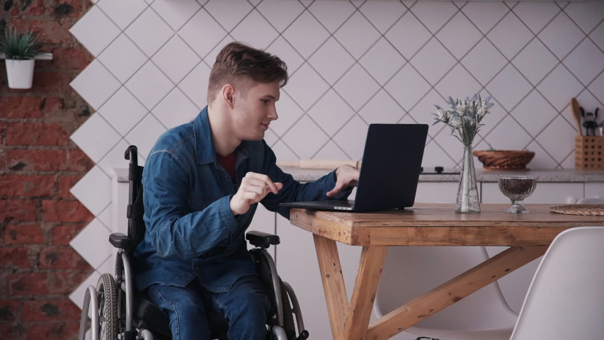Man in wheelchair working with laptop at home. Adult disabled male working studying on laptop and checking news mail. sitting in modern kitchen interior. concept computer