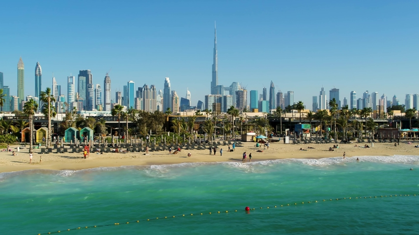 Aerial view of a luxury beach with Dubai skyscrapers at the background, U.A.E. Royalty-Free Stock Footage #1053232241
