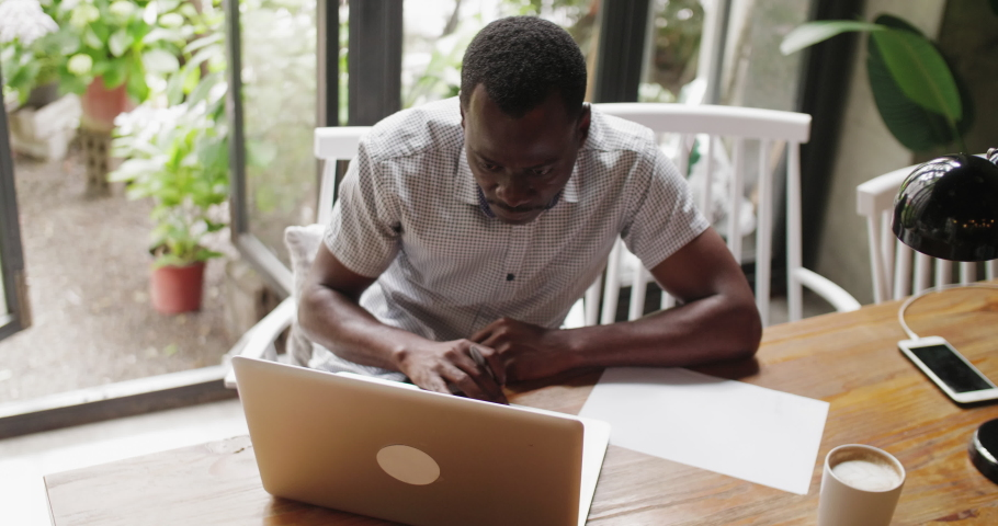 Top view of one African man typing on laptop in the office writing notes serious businessman working with laptop indoor black adult student study online