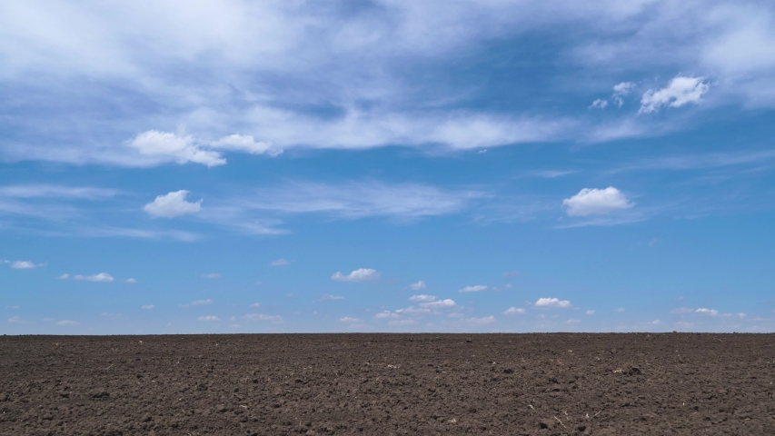 Timelapse of plowed field, soil and clouds of a bright sunny day - concept of agriculture  | Shutterstock HD Video #1053235715