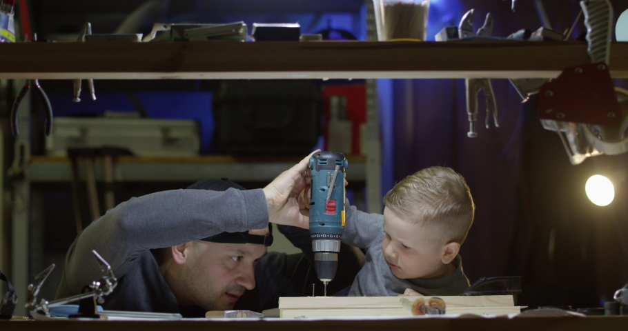 Dad Teaching Little Boy to Use Hammer Nails and Drill Working Together in Workshop a Father and Son Concept | Shutterstock HD Video #1053239000