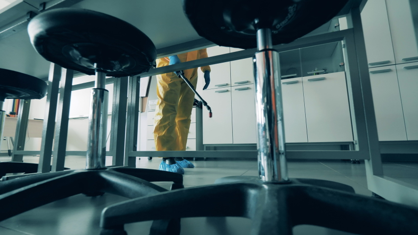 Worker disinfects room, using a sprayer. Royalty-Free Stock Footage #1053239237