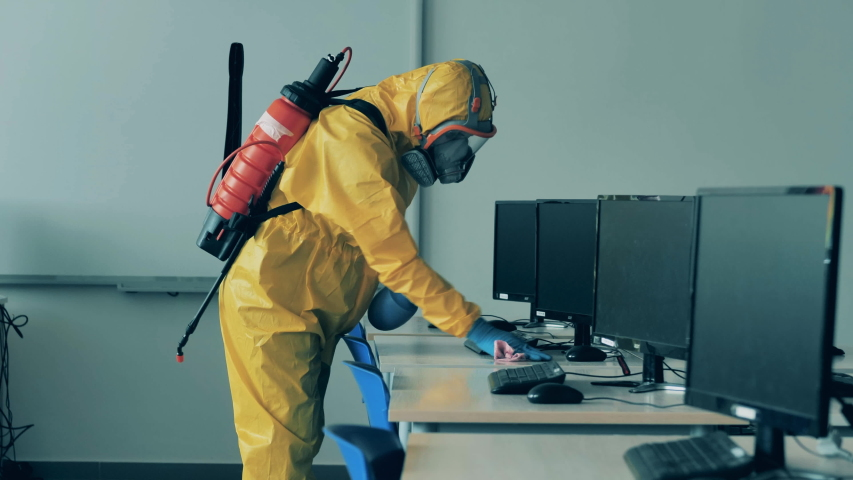 A man in a hazmat suit is disinfecting a computer class Royalty-Free Stock Footage #1053239315