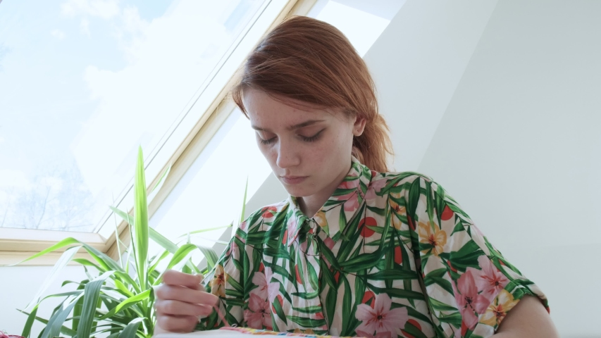 Young pretty girl in flowered summer shirt sitting at table sewing with needle. embroidery hoop, fabric with colorful pattern. Traditional hobby, lifestyle. Needlework, handicraft. quarantine leisure | Shutterstock HD Video #1053243608