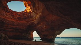 Cinemagraph / seamless video loop of a young model woman in a dress standing on the beach in the famous Benagil Cave at Algarve, Portugal at sunrise in summer with the waves of the seaing gently.
