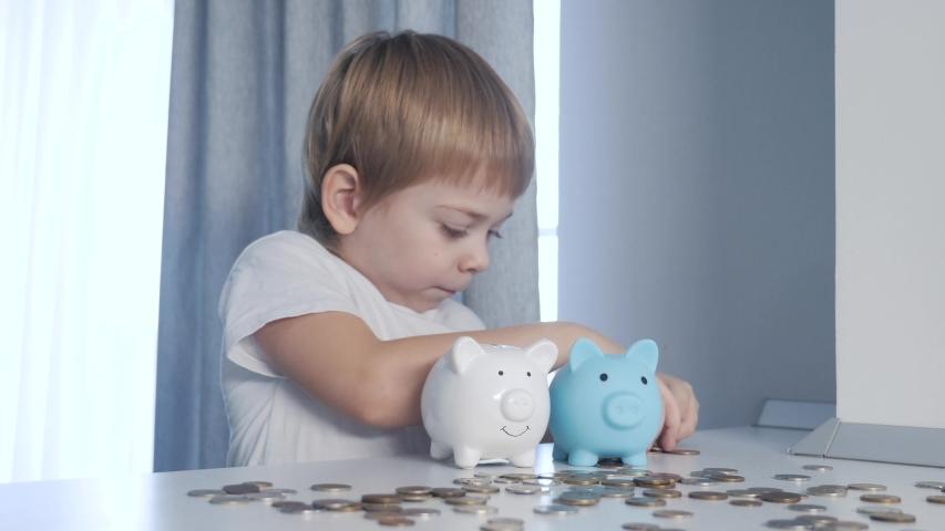Son. happy family little boy saving money concept. kid put money in lifestyle a piggy bank. child blond put coins in a piggy bank | Shutterstock HD Video #1053249089