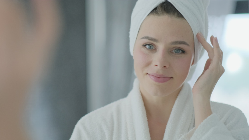 Close up portrait of young brunette woman looking in the mirror after shower at home facial skin care treatment, skincare concept.  | Shutterstock HD Video #1053249452