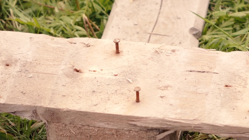 A man using a claw hammer pulls out nails from boards. | Shutterstock HD Video #1053251639