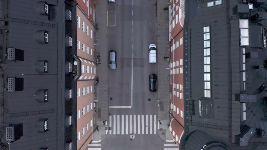Empty street in Stockholm city, Sweden aerial top down view. Quarantined city, empty abandoned streets during corona virus outbreak. Drone footage flying over buildings, parked cars and street | Shutterstock HD Video #1053257696