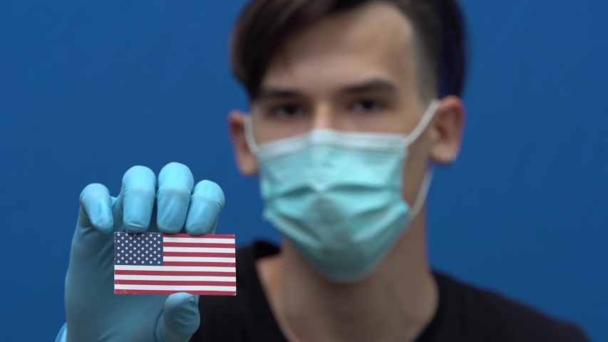 George Floyd protests. COVID-19 pandemic in United States of America. A young authentic American man in protective medical mask and gloves holding the US flag. Coronavirus pandemic in America