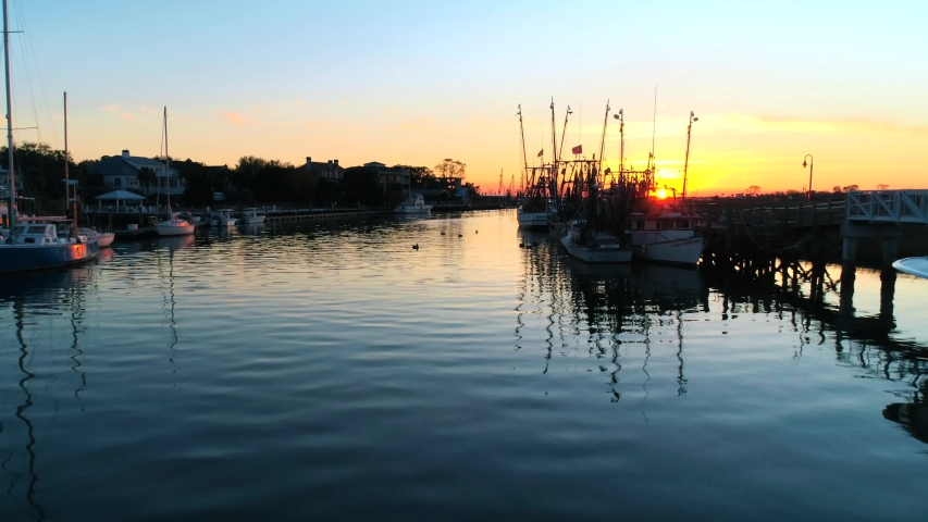 Shrimp Boats reflecting in the water at sunset. Filmed at Shem Creek in Mount Pleasant, SC. Just outside of Charleston, South Carolina. Royalty-Free Stock Footage #1053262409