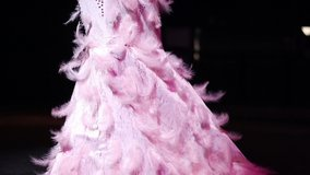 blur and defocus video footage, lovely young woman in a feather costume dancing in the pink neon light at a nightclub.