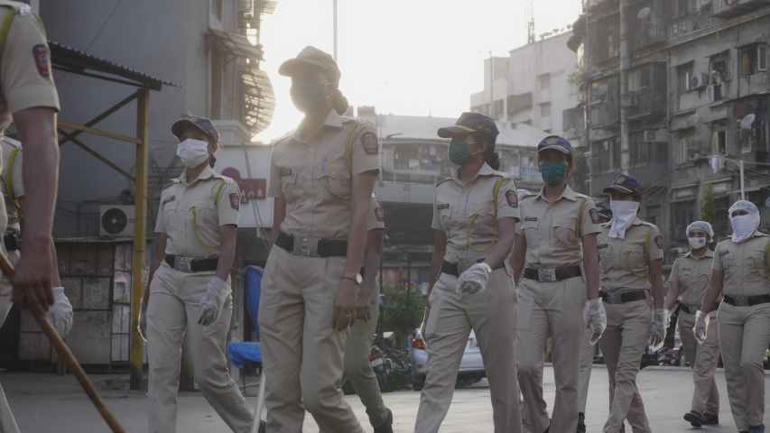 On duty ladies or women police force, constables in uniform marching on the road wearing proactive face mask during city lockdown amid coronavirus or COVID. 19 pandemic in Mumbai, India (May 2020)