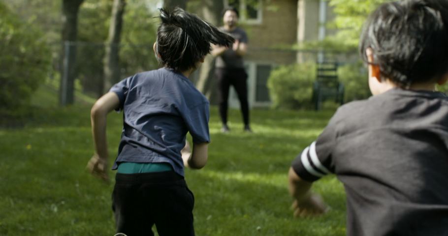Brothers excitedly run into their father's arms. Loving family fathers day.  Shot in slow-motion on RED camera in 4k.   Royalty-Free Stock Footage #1053268703