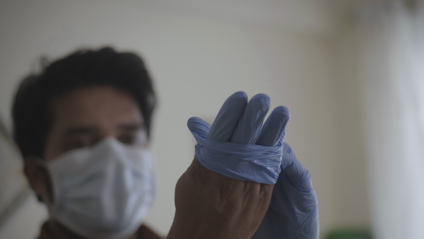 A close up shot of a male essential health worker following safety measures by wearing hand gloves amid coronavirus or COVID 19 epidemic or Pandemic