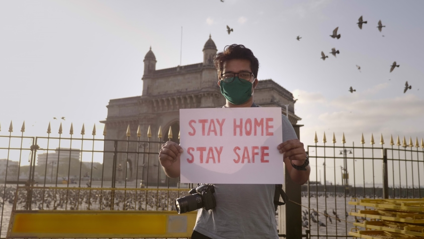 A young man wearing face mask standing and holding a placard with message 'Stay home stay safe' during city lockdown amid coronavirus in front of Gateway of India with pigeons flying in back. Royalty-Free Stock Footage #1053268943