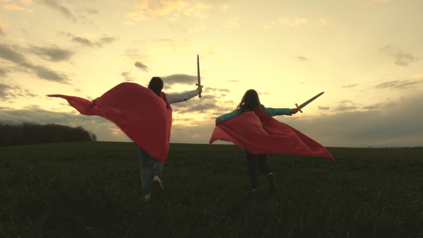 Girls in red cloaks run with swords in hand across field playing medieval knights. children fight with toy sword. children play knights. happy childhood concept. healthy young girls play super heroes | Shutterstock HD Video #1053271388