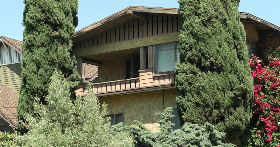 An upscale house exterior, establishing shot with a locked off angle during the day. Brown stucco & wood craftsman home, house or apartment with trees and flowers. Native 10bit 422 prores  | Shutterstock HD Video #1053271466