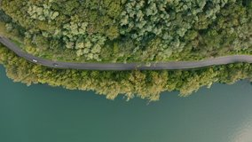 Top view on a road with a moving cars. Aerial view on a lane between forest and Lake Come. Car driving through the pine wood close to green water.
