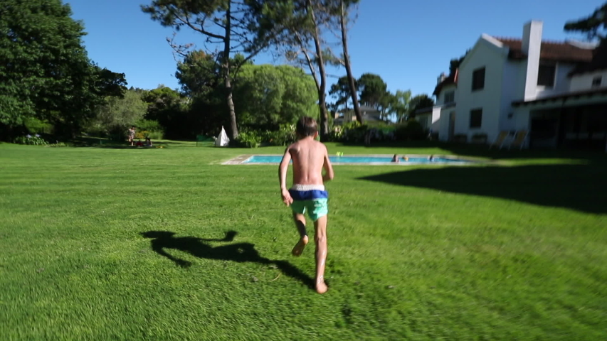 Child boy running, sprinting in home backyard garden and doing a back flip into swimming pool water. | Shutterstock HD Video #1053274409