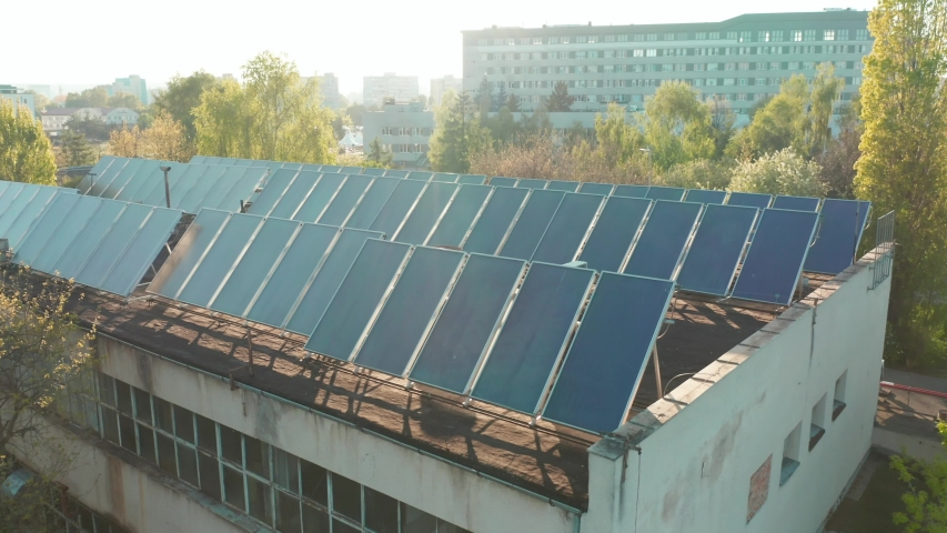 Drone flight fly over solar panels renewable green alternative energy concept. Aerial view of the solar panels on the roof of an abandoned factory building. Ecology Power Conservation Concept.