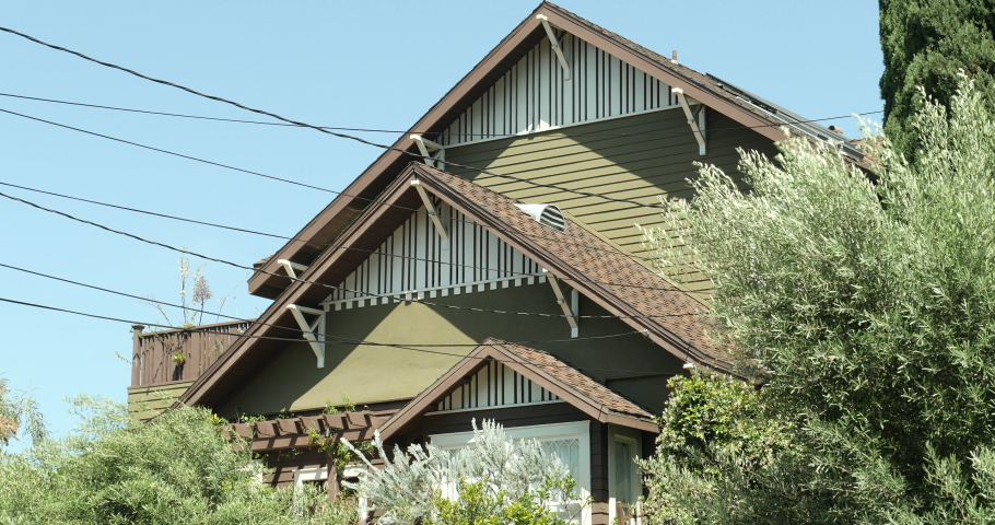 An upscale house exterior, establishing shot with a locked off angle during the day. Green panel wood craftsman home, house or apartment with trees and flowers. Native 10bit 422 prores  | Shutterstock HD Video #1053281234