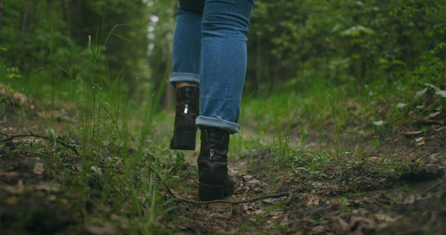Close up of women legs hiking steep terrain in slow motion. Feet in Hiking Boots Walking on Autumn Road. woman feet tracking on fall day outdoors, walking through woodland