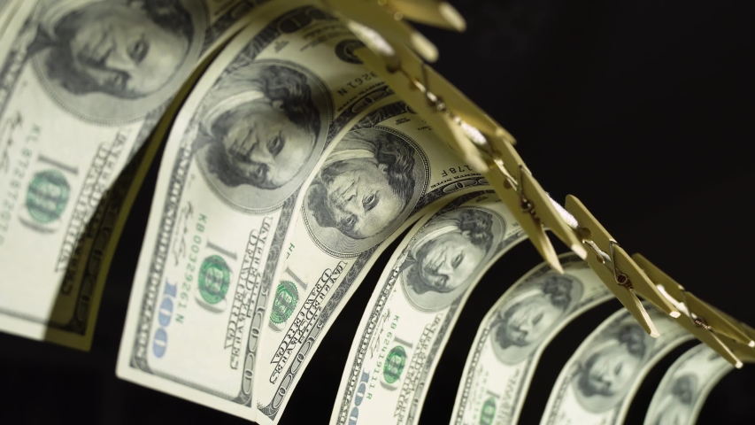 Dollars dry on a clothespin rope. The financial concept of the dollar. Hundred dollar bill on a rope. Money laundering concept. | Shutterstock HD Video #1053282335