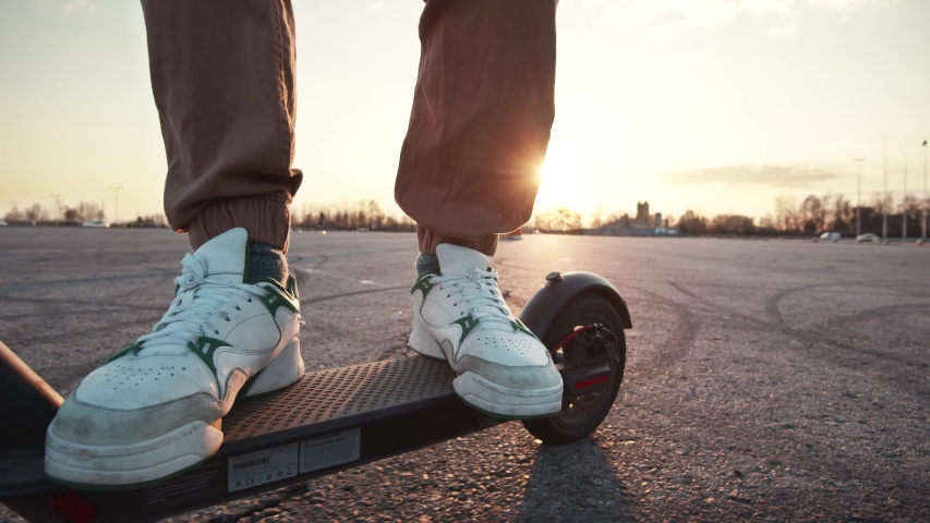 Shot on legs young man in white sneakers ride on electric mobile scooter outside parking space at sunset. Beautiful scenery, nature. Eco-friendly transportation. | Shutterstock HD Video #1053283751