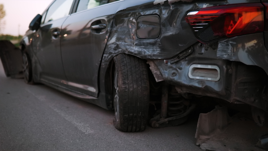 Wrecked new black car on road backside view | Shutterstock HD Video #1053287576