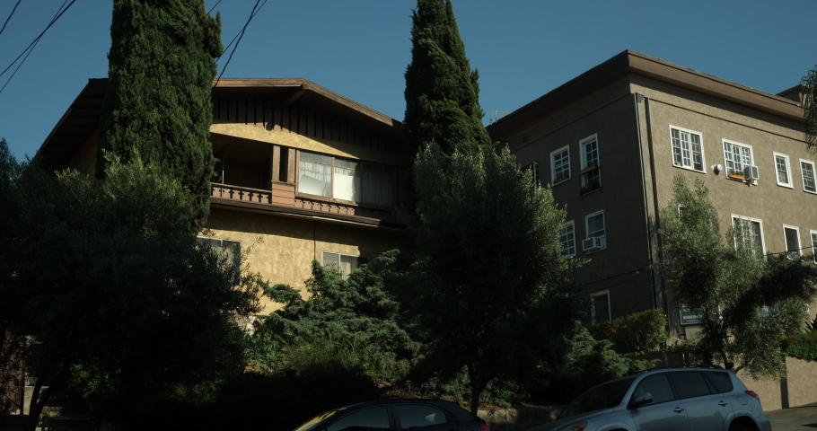 An upscale house exterior, establishing shot with a locked off angle during the day. Brown stucco & wood craftsman home, house or apartment with trees and flowers. Native 10bit 422 prores  | Shutterstock HD Video #1053288479