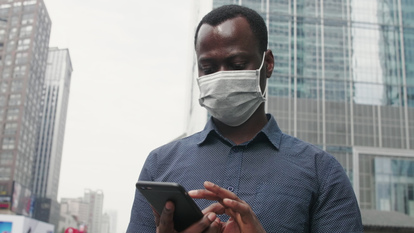 low angle close up of one black man wear mask talking on the phone comfort friend be strong in the street city urban place during pandemic of coronavirus Covid-19 Royalty-Free Stock Footage #1053290732