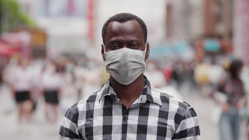 Slow motion of one black African man wear face mask looking at camera smile in the eye at urban street with crowd of people walking in blurred background coronavirus Covid-19 pandemic outbreak