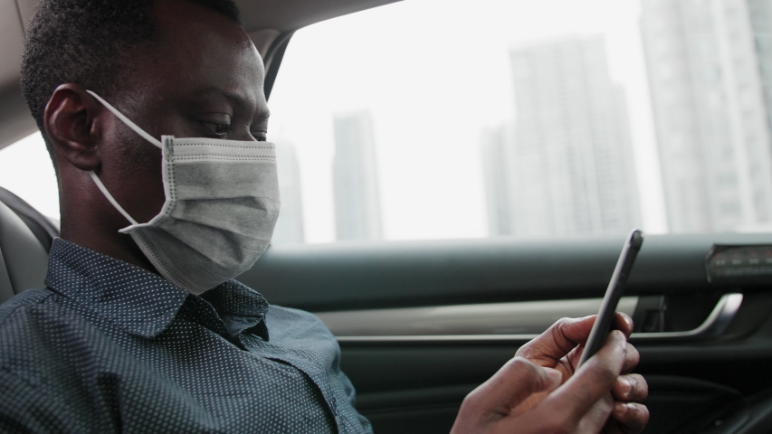 Side view of one black businessman wear mask traveling in the car using mobile phone looking at phone in hand during pandemic of coronavirus Covid-19