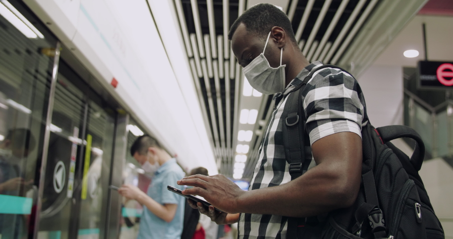 Side view of one black man wear mask in the subway using mobile phone passengers in the train all with mask during pandemic of coronavirus Covid-19 | Shutterstock HD Video #1053290774