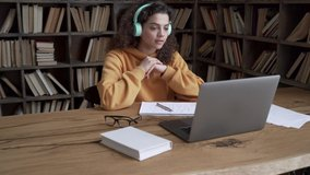 Hispanic teen girl, latin young woman school college student wear headphones learn watching online webinar webcast class looking at laptop elearning distance course or video calling teacher by webcam.