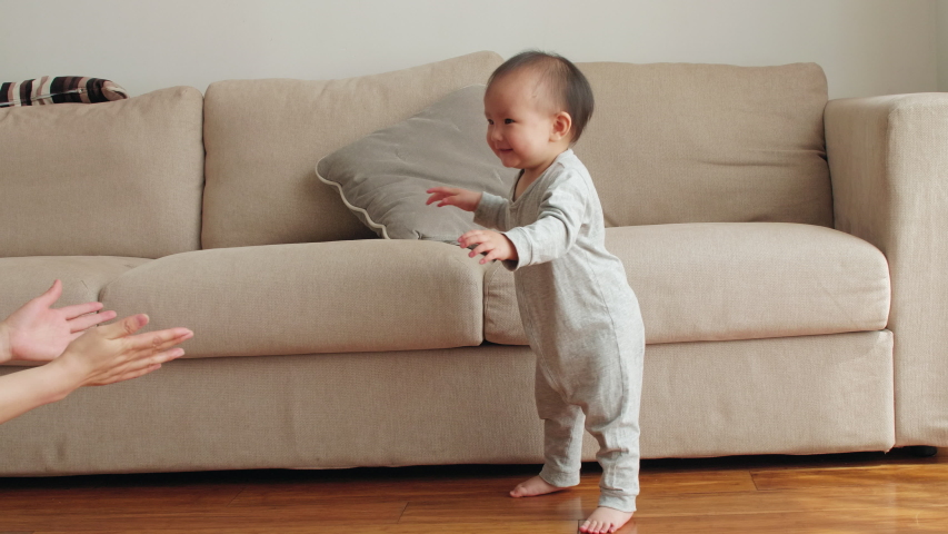 Slow motion of lovely asian baby girl learning to walk taking first step walk to her mother at home Chinese baby girl walking on the floor with bare foot  | Shutterstock HD Video #1053292667