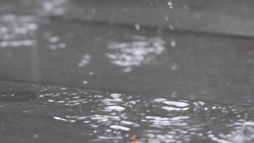 Slow motion speed close up scene on raindrop fall against and bounce on floor, flood from rainstrom in bad rainy day, natural pattern of pouring rain bumping on ground, grainy texture of water