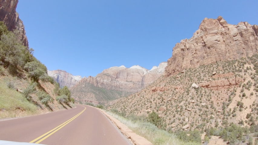 Car mounted camera, driving trough stunning mountain landscape in Wester USA. Point of view vehicle driving in Zion National Park. Road trip freedom concept  | Shutterstock HD Video #1053295871