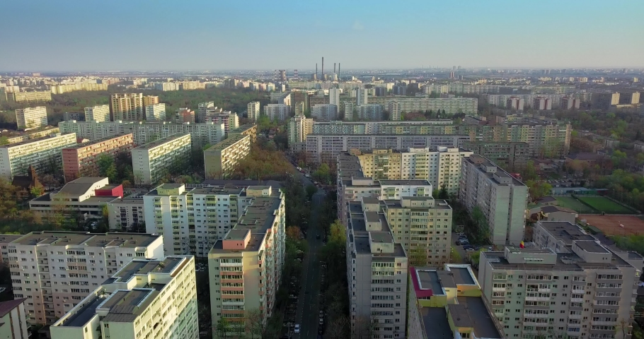 Aerial view drone shot of apartment buildings in a lock down city during corona virus outbreak, blue sky and sunset sun, no people and no cars Europe romania bucharest trees and cars | Shutterstock HD Video #1053297764