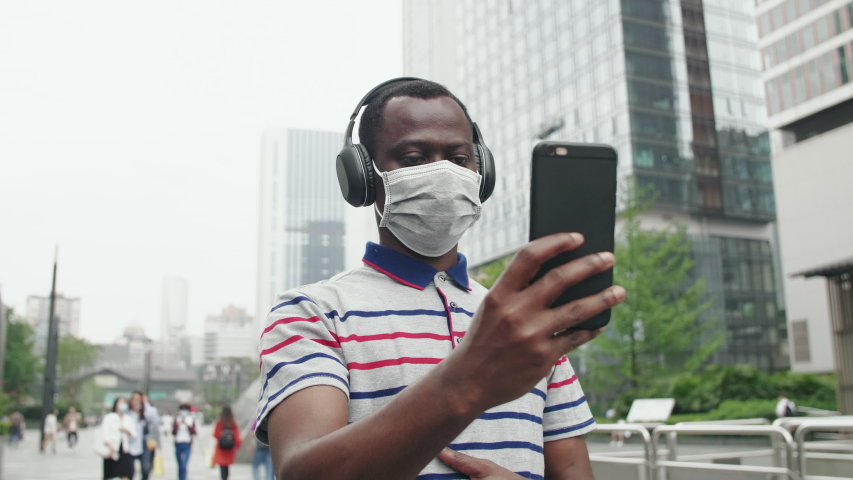 close up of one Black man wear mask video chatting on the phone in the street during coronavirus Covid-19 pandemic African man talking to friend on mobile phone with crowd people wear mask in city Royalty-Free Stock Footage #1053303170