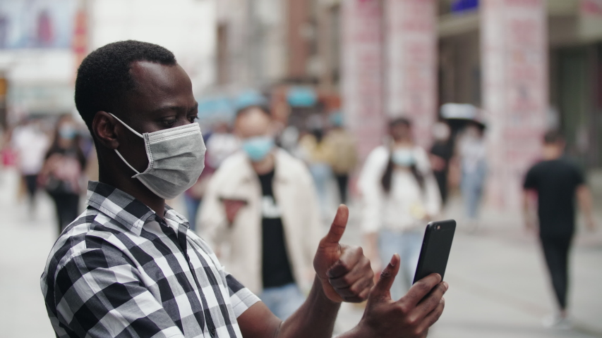 Slow motion of one Black man wear mask video chatting on the mobile phone encourage friend be strong in crisis in the street during coronavirus Covid-19 pandemic with crowd people wear mask in city Royalty-Free Stock Footage #1053303665