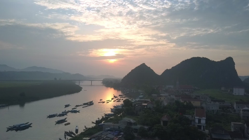 Motion to high bridge over wide calm river surrounded by tiny boats and village against beautiful sunset sky | Shutterstock HD Video #1053304850