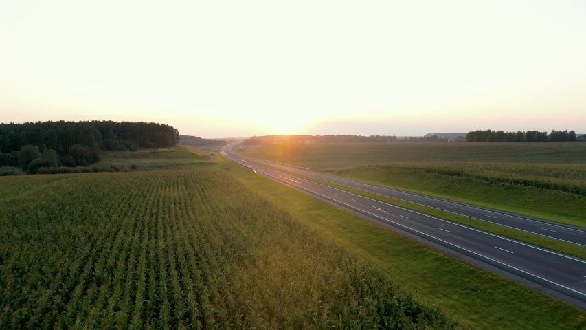 Aerial flying forward through the picturesque countryside with corn agricultural fields towards the sunset. Intercity modern highway with driving vehicles. Golden colors of sun rays | Shutterstock HD Video #1053305045