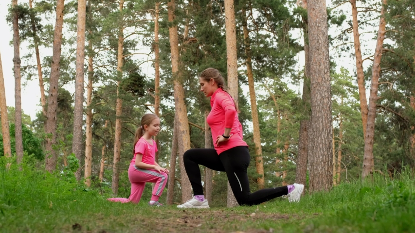 Young sporty mother and little cute daughter doing fitness training exercise together in a forest. | Shutterstock HD Video #1053307520