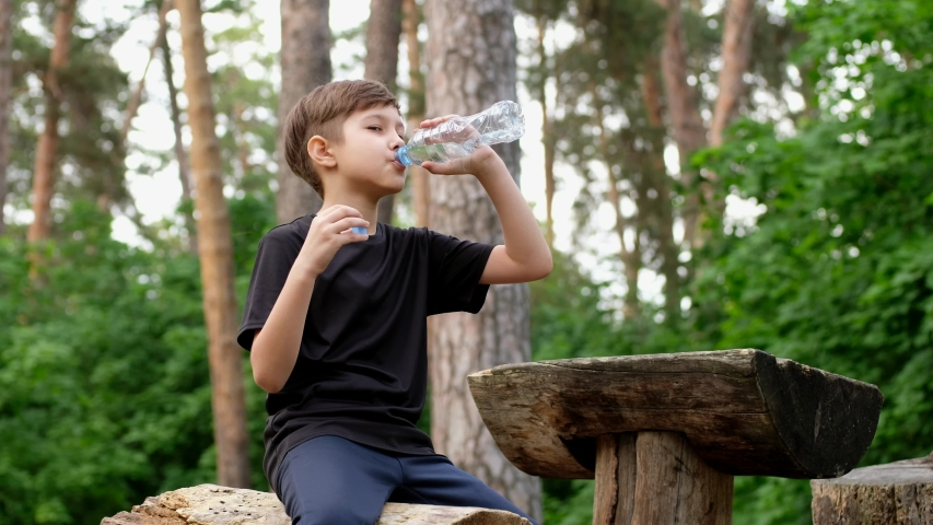 Little boy drinking water from a bottle after playing sports. Child resting after running.   Shutterstock HD Video #1053308081