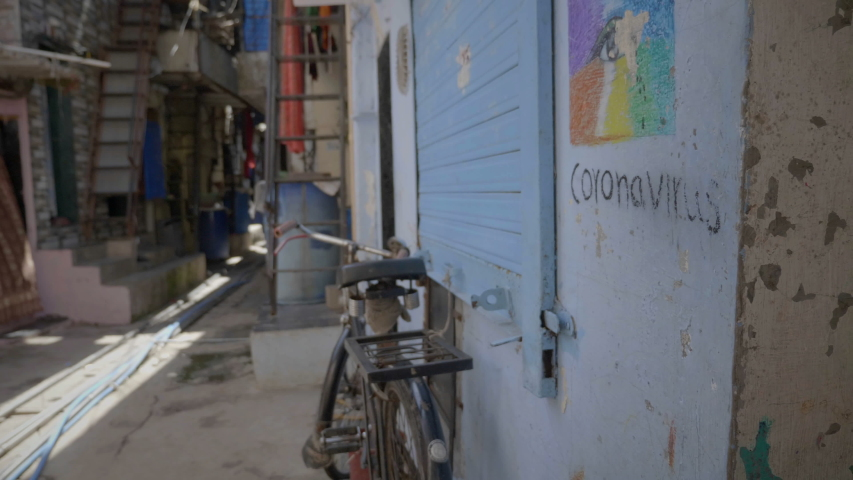 A movement shot of empty lane closed shops and art work graffiti about coronavirus awareness is drawn on the wall in slums during lockdown amid coronavirus COVID19 epidemic pandemic in India