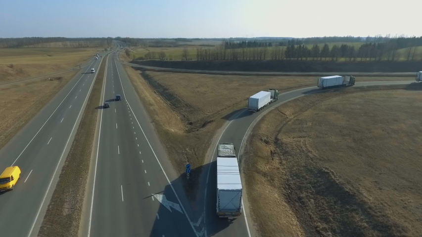 A lot of trucks turn off the road and go around the ring. A column of trucks moving along the overpass to the bridge Royalty-Free Stock Footage #1053318185